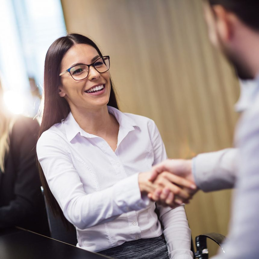 A female interviewee shakes hands with her employer at a job interview